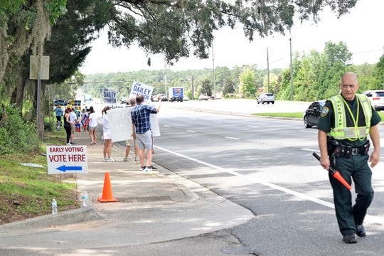 Supporters waved signs on Thomasville Road outside the Northeast Branch Library Saturday to encourage early voters. More than 600 votes were cast at the library Saturday.