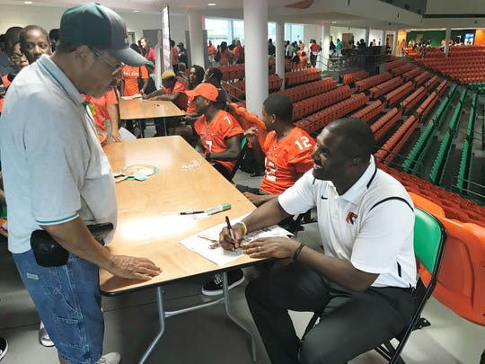 Football head coach Willie Simmons signs the football poster for Bill Adams during FAMU Fan Day inside the Al Lawson Multipurpose Center in 2018. The entire team and coaching staff will be doing the same thing again on Saturday, Aug. 17.
