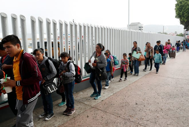 This July 26 photo shows people lining up to cross into the U.S. to begin the process of applying for asylum near the San Ysidro port of entry in Tijuana, across the border fro San Diego.