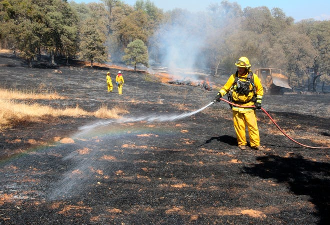 Higgins Fire Protection District firefighters spread water on smoldering spots of the Wolf Incident that burned vegetation in the California community of Grass Valley on Wednesday.