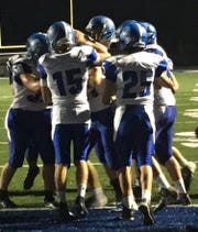 Members of the Amherst football team celebrate a touchdown run by quarterback Lincoln Cullen during the third quarter of a win over Merrill on Friday.