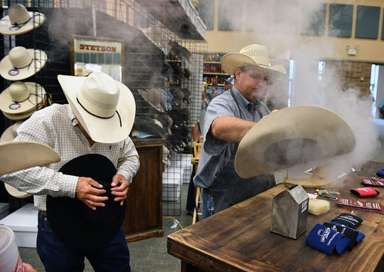 Garry Giese, left, and James Andrae of Capital Hatters use steam to help shape the perfect creases for customers'  cowboy hats Saturday at the Texas Ranch Roundup at the Ray Clymer Exhibit Hall.