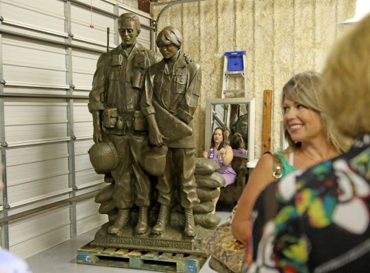 "Members of the Major Francis Grice Chapter National Society Daughters of the American Revolution get their first look at the Vietnam Memorial sculpture titled ""For Those We Shall Never Forget"" by Garland Weeks Saturday, Aug. 18, 2018, after their first meeting of the season. The sculpture is made of bronze and will be installed in the Veterans Plaza area of the Lake Wichita project."