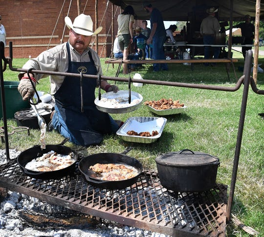 Valente Uribe of the Tongue River Ranch cooks chicken fried steak over an open fire during the Ranch Cooking competition Saturday at the Texas Ranch Roundup at the Kay Yeager Coliseum.