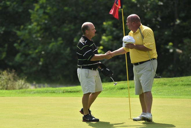 Brad Baker (left) shakes hands with Mike Walters on the 18th hole after Saturday's final round of the ZDGA Seniors. Baker won the event and is the first person to hold the Amateur and Senior titles at the same time.