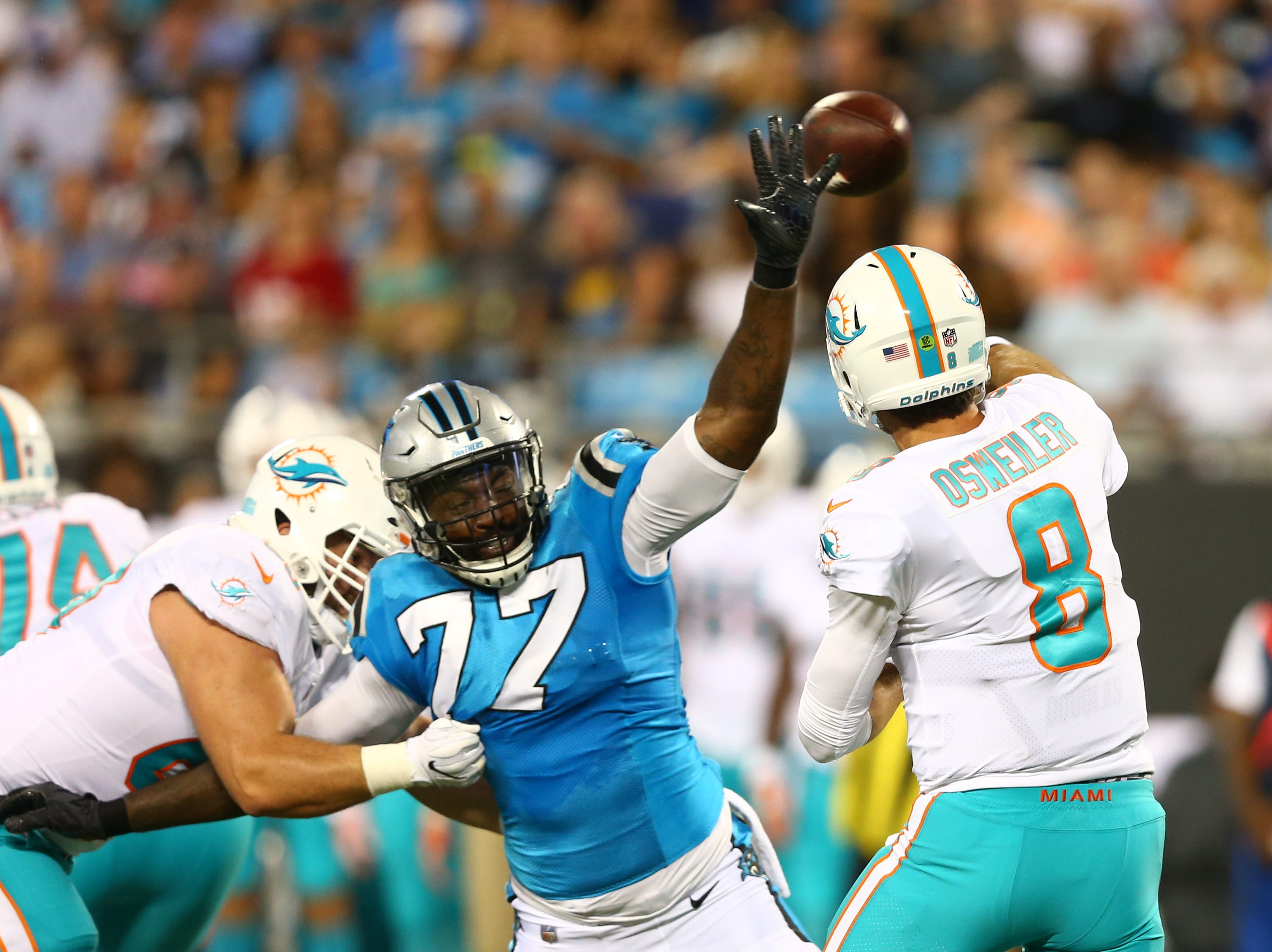 Miami Dolphins quarterback Brock Osweiler (8) passes the ball while under pressure of Carolina Panthers defensive end Zach Moore (77) in the second quarter at Bank of America Stadium.