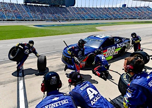 Rowdy Harrell, far left, carries a pair of tires during a pit stop for Hendrick Motorsports driver Alex Bowman.