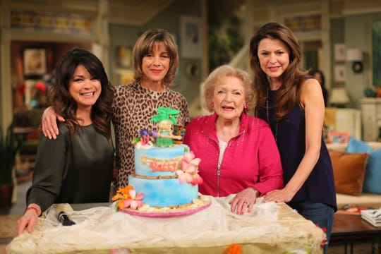 "Betty White, second from right, receives a cake on her 93rd birthday in 2015. She's joined by her ""Hot in Cleveland"" co-stars Valerie Bertinelli, left, Wendie Malick and Jane Leeves."