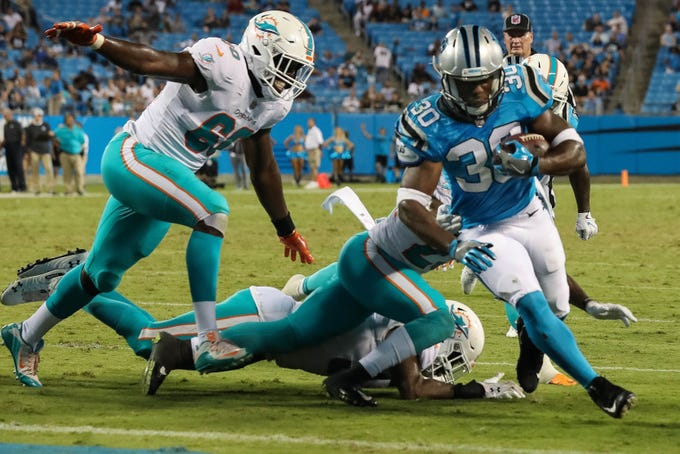 Carolina Panthers running back Elijah Hood (30) runs away from Miami Dolphins defensive end Claudy Mathieu (60) towards the goal line during the second half at Bank of America Stadium.