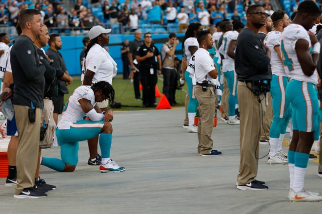 Miami Dolphins' Albert Wilson (15) kneels during the national anthem before a preseason NFL football game against the Carolina Panthers in Charlotte, N.C., Friday, Aug. 17, 2018.