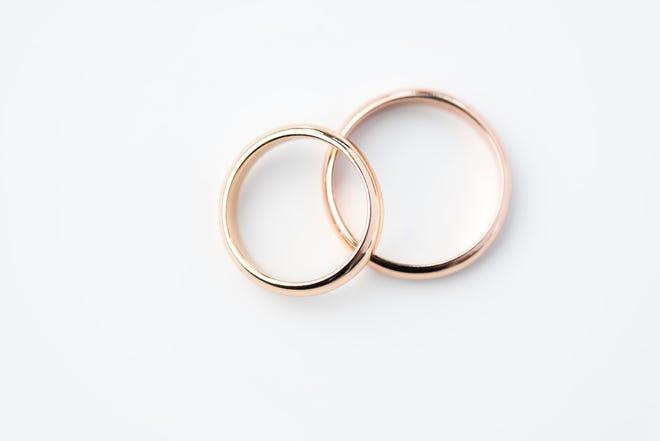 Two golden wedding rings on white.