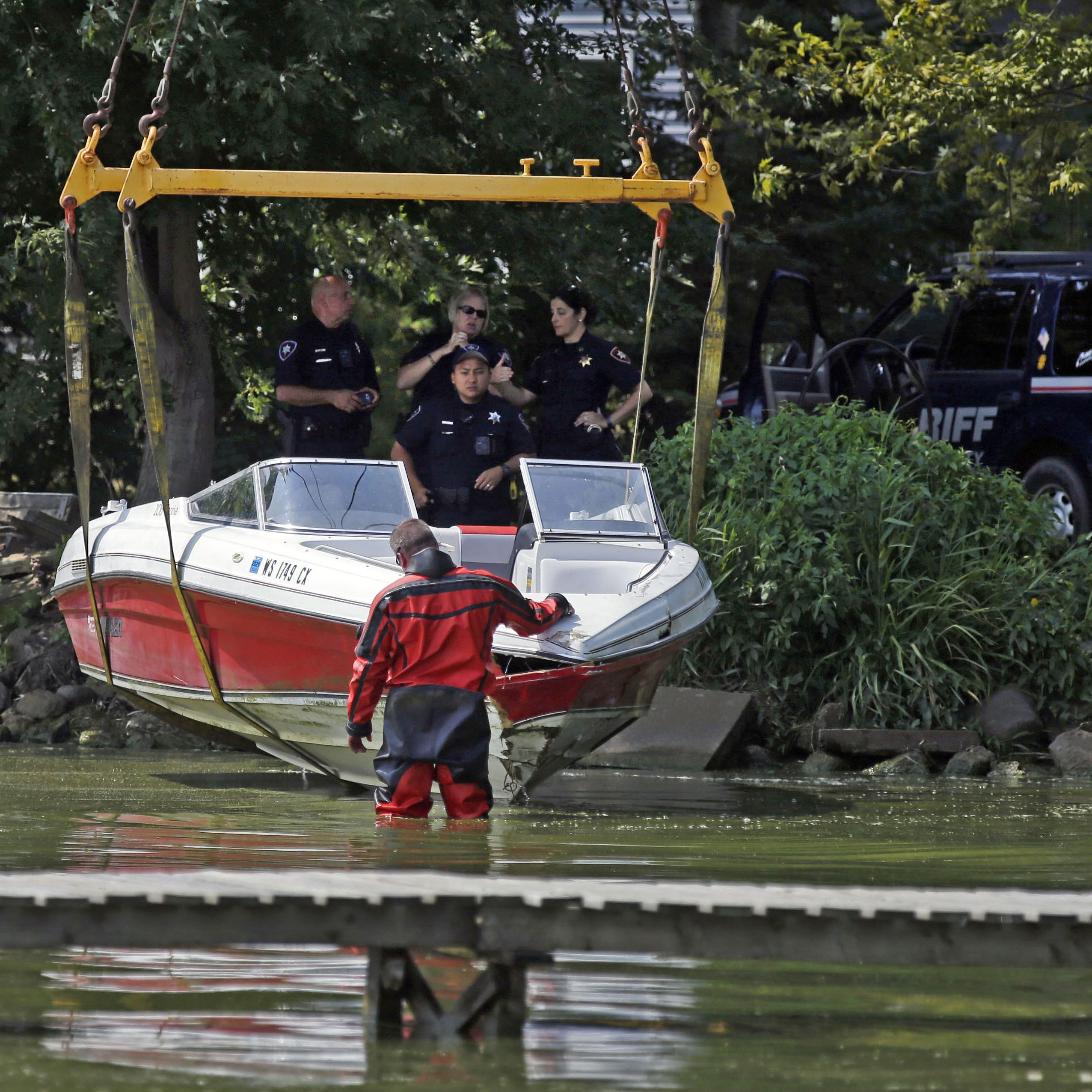 Jason Rippl, a member of the Winnebago County Sheriff's Department Rescue and Recovery Dive Team, inspects a 20-foot Rinker Captiva boat Sunday as it is removed from Lake Winnebago. The boat was damaged in a collision with another boat Saturday.