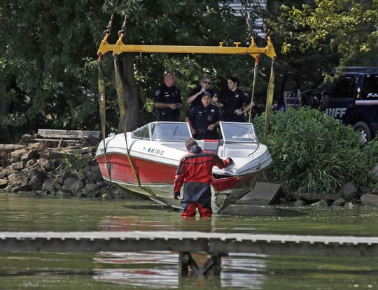 Jason Rippl, a member of the Winnebago County Sheriff's Department Rescue and Recovery Dive Team, inspects a 20-foot Rinker Captiva boat Aug. 19 as it is removed from Lake Winnebago. The boat was damaged in a collision with another boat Aug. 18.