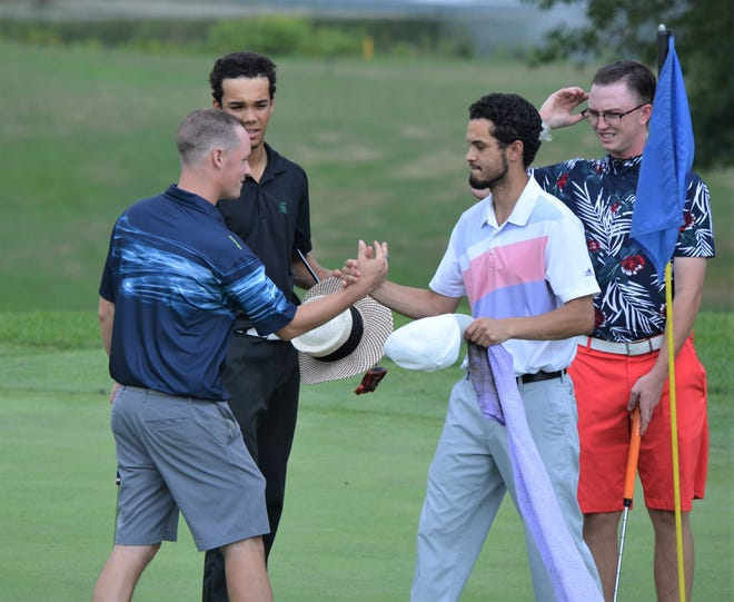 Kory Roberts, left, is congratulated by his playing group after the final hole as he won the 41st annual Calhoun County Amateur Golf Championship on Sunday at Binder Park Golf Course.