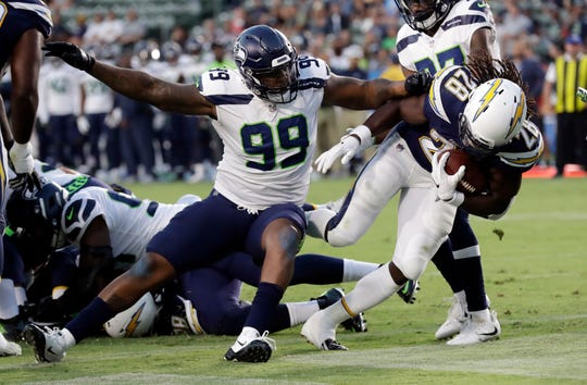 Los Angeles Chargers running back Melvin Gordon (right) scores a rushing touchdown past Seattle Seahawks defensive tackle Quinton Jefferson (99).