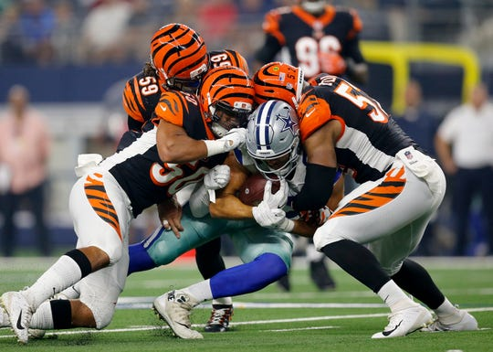 Dallas Cowboys tight end Geoff Swaim (87) is brought down by Cincinnati Bengals linebacker Jordan Evans (50) and linebacker Preston Brown (52) after a catch in the first  quarter of the NFL Preseason Week Two game between the Dallas Cowboys and the Cincinnati Bengals at AT&T Stadium in Arlington, Texas, on Saturday, Aug. 18, 2018.