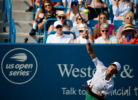 Novak Djokovic serves to Roger Federer during the Western & Southern Open Men's finals match at the Lindner Family Tennis Center in Mason on Sunday.