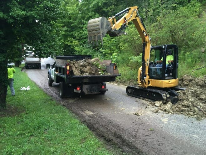 A Covington Public Works crew worked Friday morning to clear Amsterdam Road. The crew included, from left: grounds worker Chad Hyland (walking), laborer James Payne (driving the dump truck), and cement brick mason Gene Kohl (operating the mini excavator).
