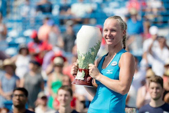 Kiki Bertens holds the trophy after defeating Simona Halep 2-6, 7-6, 6-2, in the Western & Southern Open Women's finals match at the Lindner Family Tennis Center in Mason on Sunday.