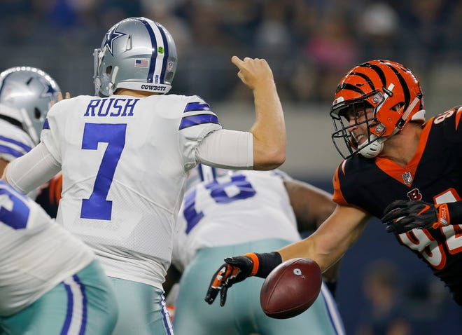 Cincinnati Bengals defensive end Sam Hubbard (94) stripes the ball from Dallas Cowboys quarterback Cooper Rush (7) for a fumble in the second quarter of the NFL Preseason Week Two game between the Dallas Cowboys and the Cincinnati Bengals at AT&T Stadium in Arlington, Texas, on Saturday, Aug. 18, 2018.