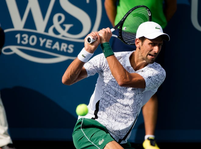 Novak Djokovic returns to Roger Federer during the Western & Southern Open Men's finals match at the Lindner Family Tennis Center in Mason on Sunday.