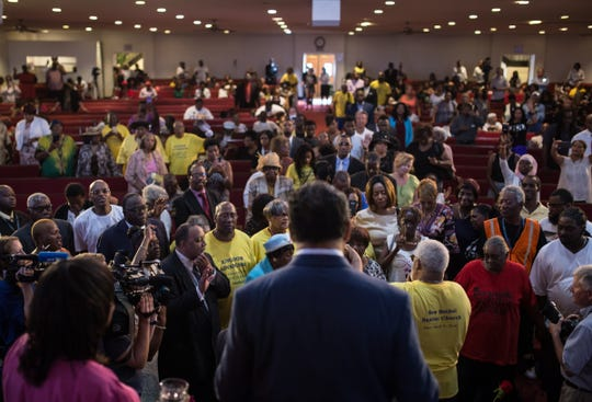 People gather around Rev. Robert Smith Jr. of New Bethel Baptist Church, right, for prayer as Rev. Jesse Jackson, center, stands on stage during a service in honor of Aretha Franklin at New Bethel Baptist Church in Detroit on Sunday, August 19, 2018.