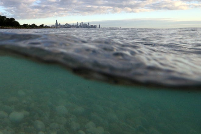 Waves hit the shoreline near Morgan Point as the Chicago skyline is seen above the surface of Lake Michigan.