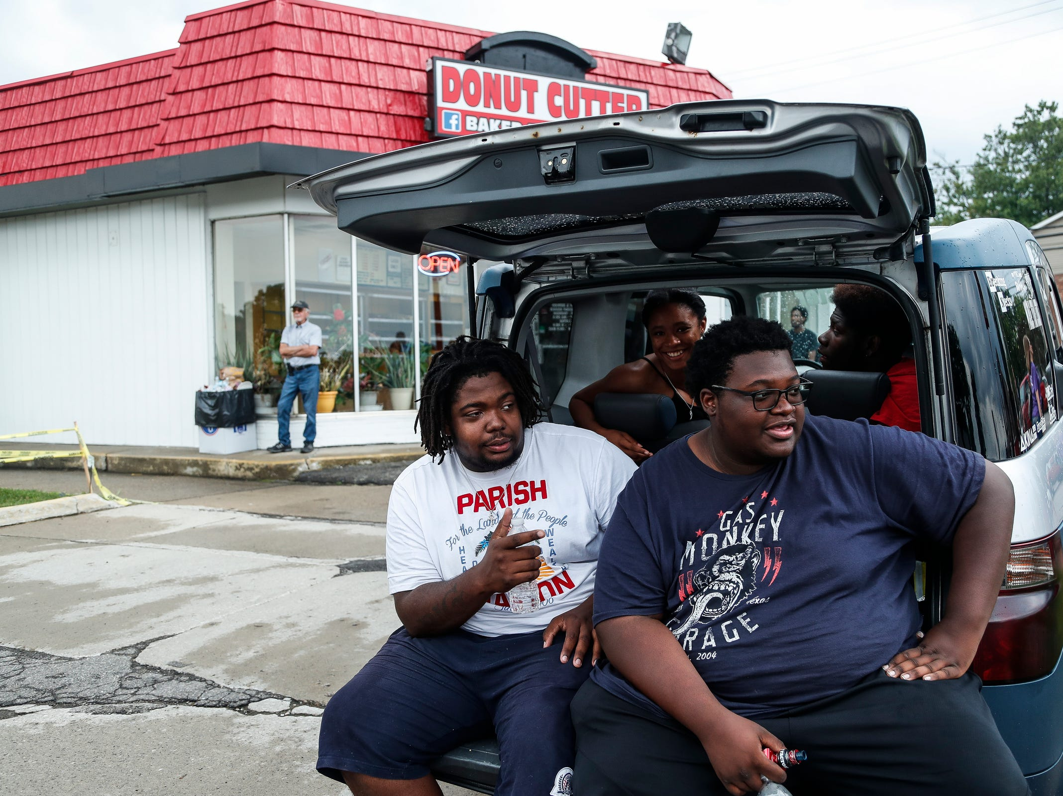 From left, Kevin Merchant of Ferndale, Kharimah Jones, Robert Jones, and Mike Davis, all of Detroit, sit in the back of a Honda Element as they watch classic and modern cars cruising along Woodward Avenue in Royal Oak during the Woodward Dream Cruise, Saturday, August 18, 2018.