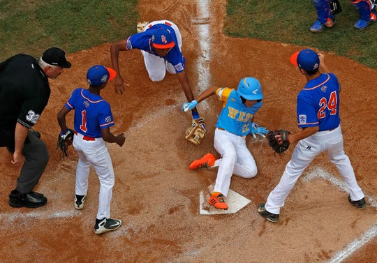 Honolulu, Hawaii's Taylin Oana, center right, gets his toe on home plate before a diving tag attempted by Grosse Pointe Woods-Shores' Jarren Purify (6), top center, after being caught in a rundown between third and home during the second inning of GPWS's 8-3 loss in United States pool play at the Little League World Series tournament in South Williamsport, Pa., Sunday, Aug. 19, 2018.