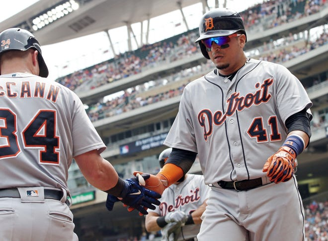 Tigers designated hitter Victor Martinez, right, is greeted by catcher James McCann after Martinez scored on a double by Jim Adduci in the first inning on Sunday, Aug. 19, 2018, in Minneapolis.
