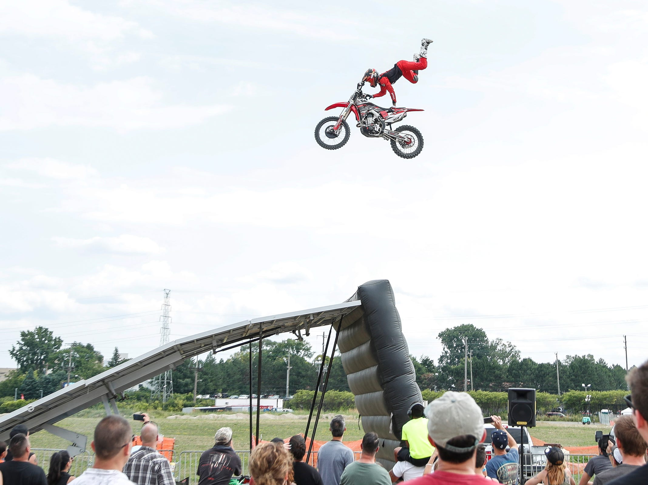 Race car fans watch a motocross exhibition during Roadkill Nights Powered by Dodge in Pontiac, Saturday, August 11, 2018.