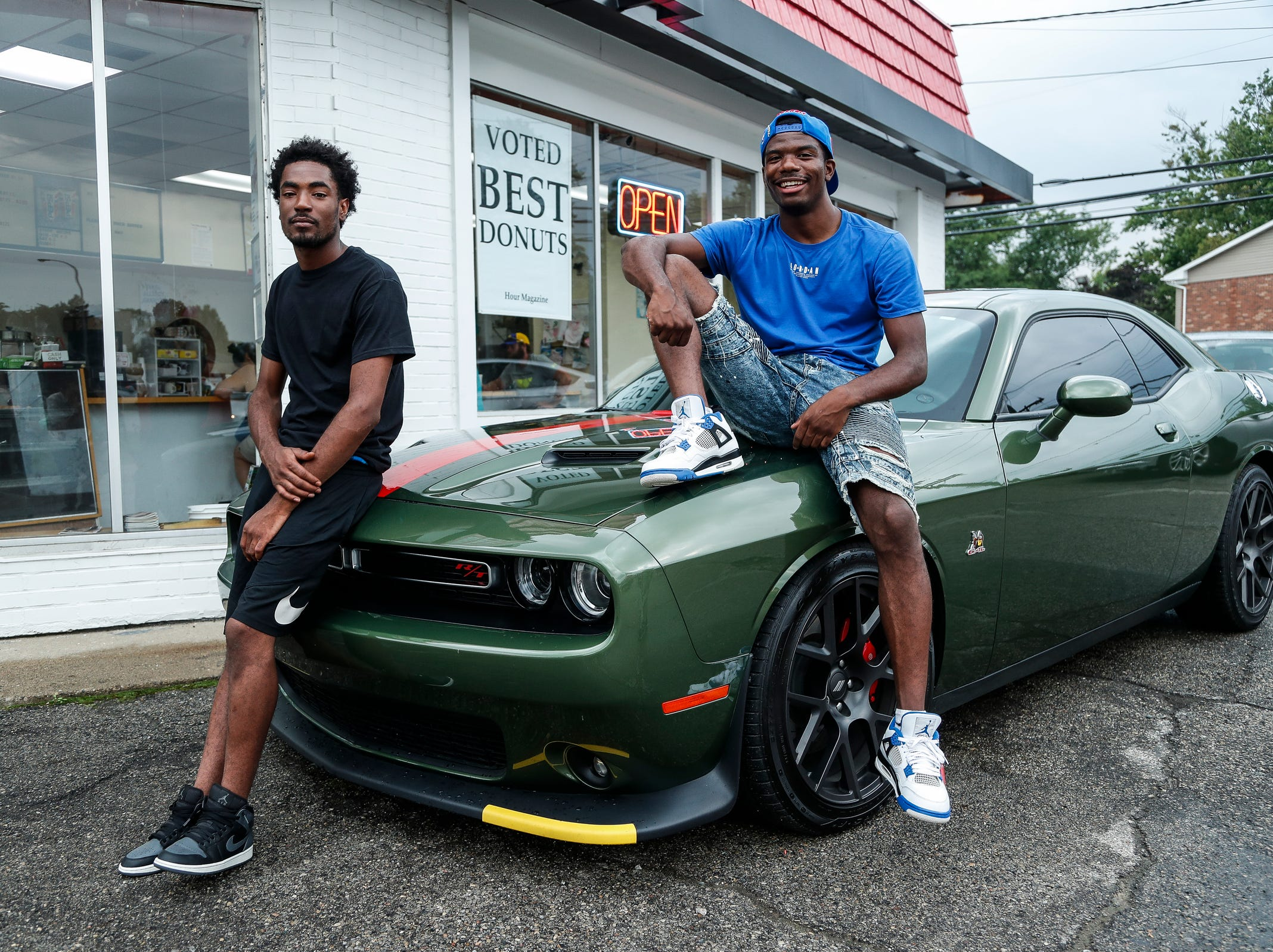 Markell Crawley, of Detroit, and his friend Harold Montgomery, of Warren, sit on Montgomery's 2018 Dodge Challenger Scat Pack as they watch classic and modern cars cruising along Woodward Avenue in Royal Oak during the Woodward Dream Cruise, Saturday, August 18, 2018.