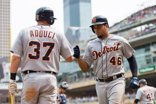 Tigers first baseman Jim Adduci congratulates third baseman Jeimer Candelario after scoring in the sixth inning of the Tigers' 5-4 loss on Sunday, Aug. 19, 2018, in Minneapolis.