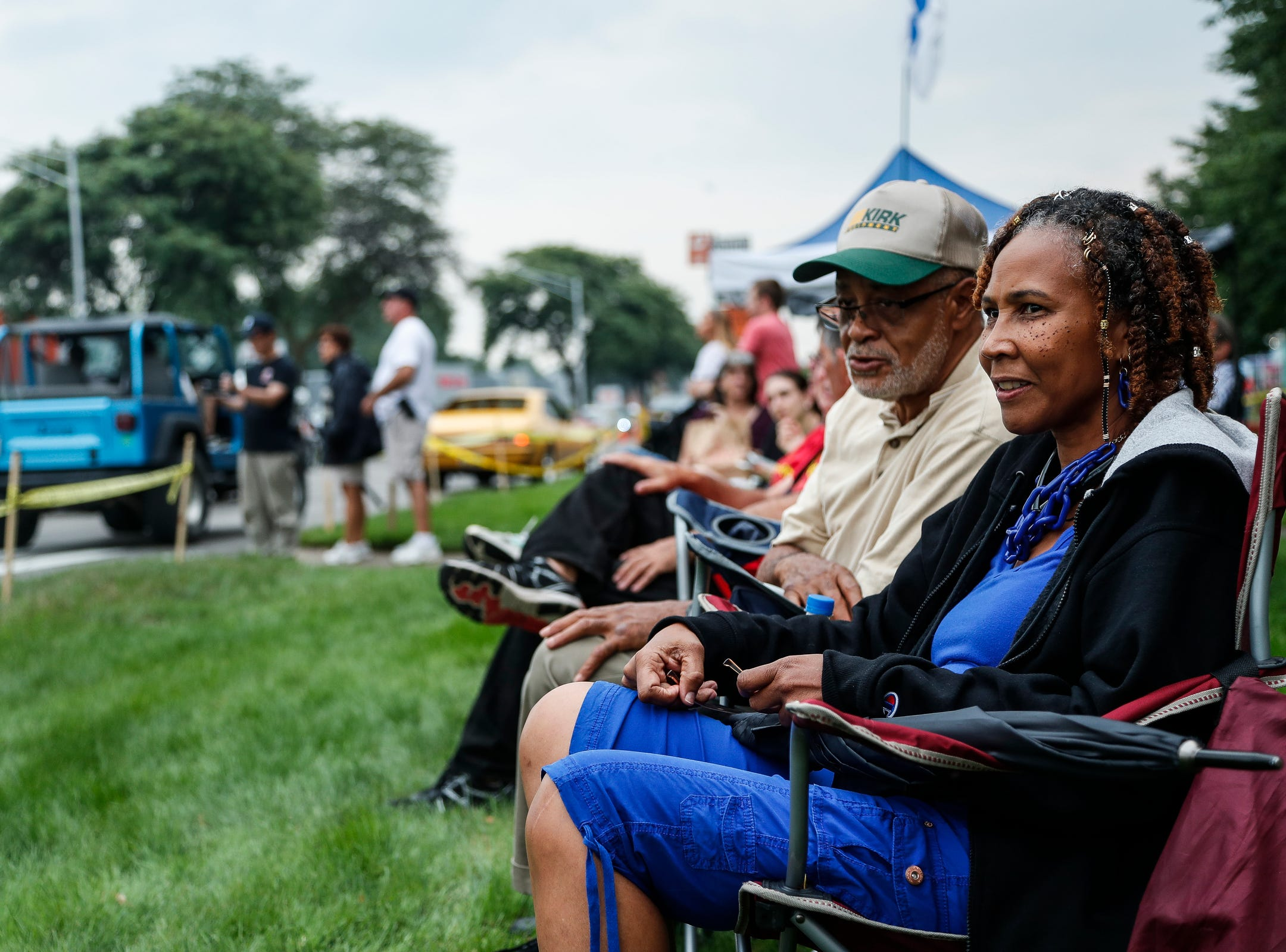 Michelle Jackson and her friend Vernon Tounsel, both of Southfield, sit near Woodward Avenue and Catalpa Drive and watch classic and modern cars cruising along Woodward Avenue in Royal Oak during the Woodward Dream Cruise, Saturday, August 18, 2018.