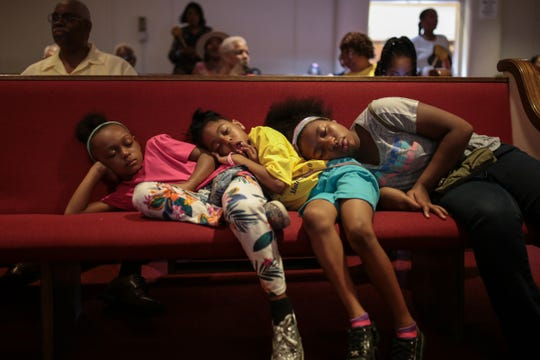 From left,  Madison Rivers, Kimora Caver and Tamijes Hill, all of Detroit, lean on each other as they nap in a pew before the Rev. Jesse Jackson to the stage for a prayer service on honor of Aretha Franklin at New Bethel Baptist Church in Detroit on Sunday, August 19, 2018.