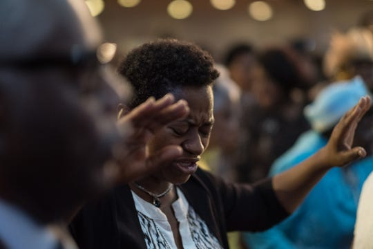 A woman raises her hands in prayer as Rev. Jesse Jackson speaks during a service in honor of Aretha Franklin at New Bethel Baptist Church in Detroit on Sunday, August 19, 2018.