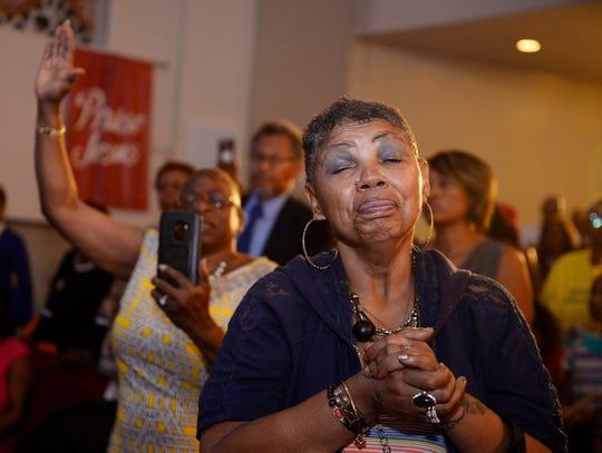 Minister Sandrea Bell of Detroit prays during the sermon by the Rev. Jesse Jackson