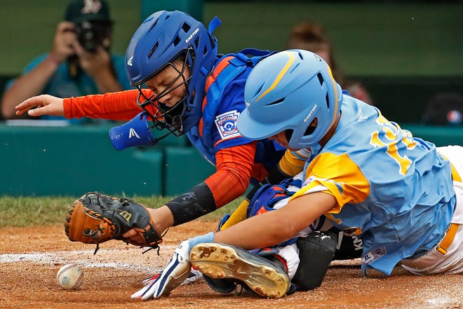 Hawaii's Mana Lau Kong scores as Grosse Pointe Woods-Shores' Jake Martin drops the ball during the second inning.