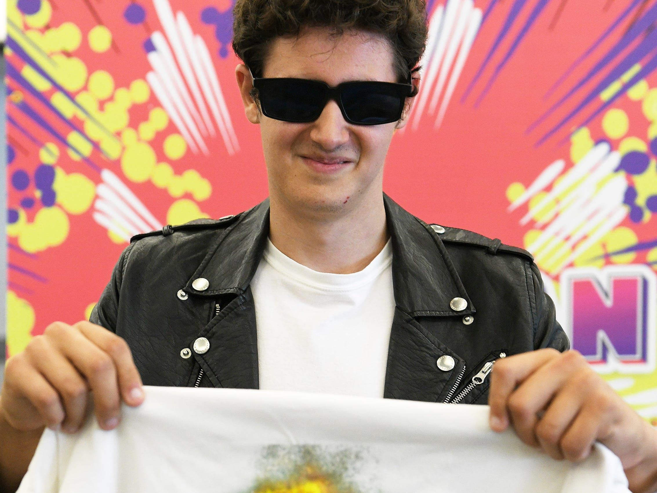"Johnny Gary, 21, of Pinckney shows a t-shirt of himself in character of ""Danny Zuko"" from the movie Grease."