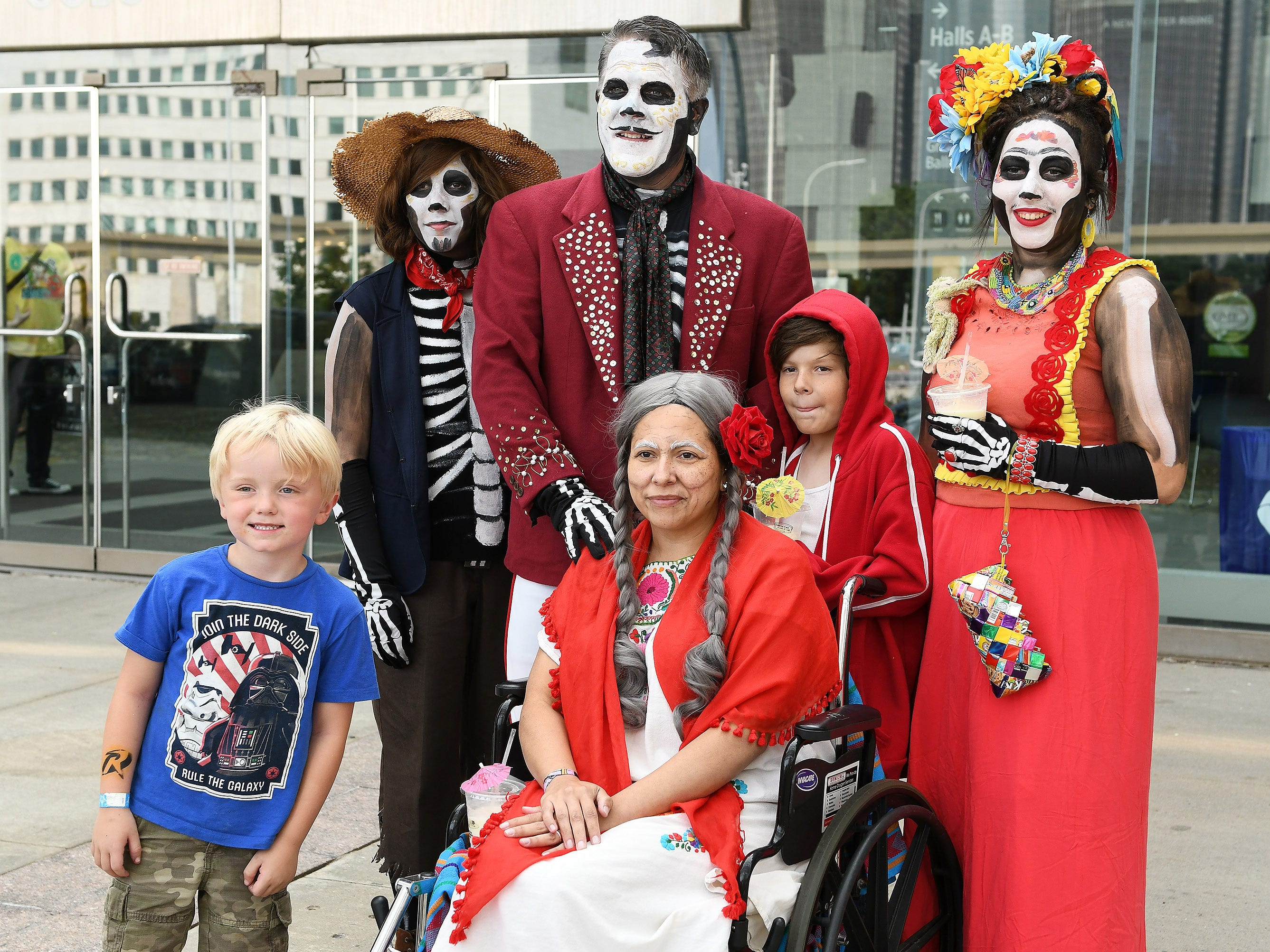 "Clay White-Hessling, left, 5, of Southgate gets in a group photo with the Shelton family from Bruce Township, who are dressed as characters from the movie ""Coco."" The Shelton family is Josette, 42, as ""Mama Coco,"" seated front, and from left, Reina, 13, as ""Hector"", Charlie, 44, as ""Ernesto de la Cruz"", Elisha, 9, as ""Miguel"" and Rica, 19, as Frida Kahlo."