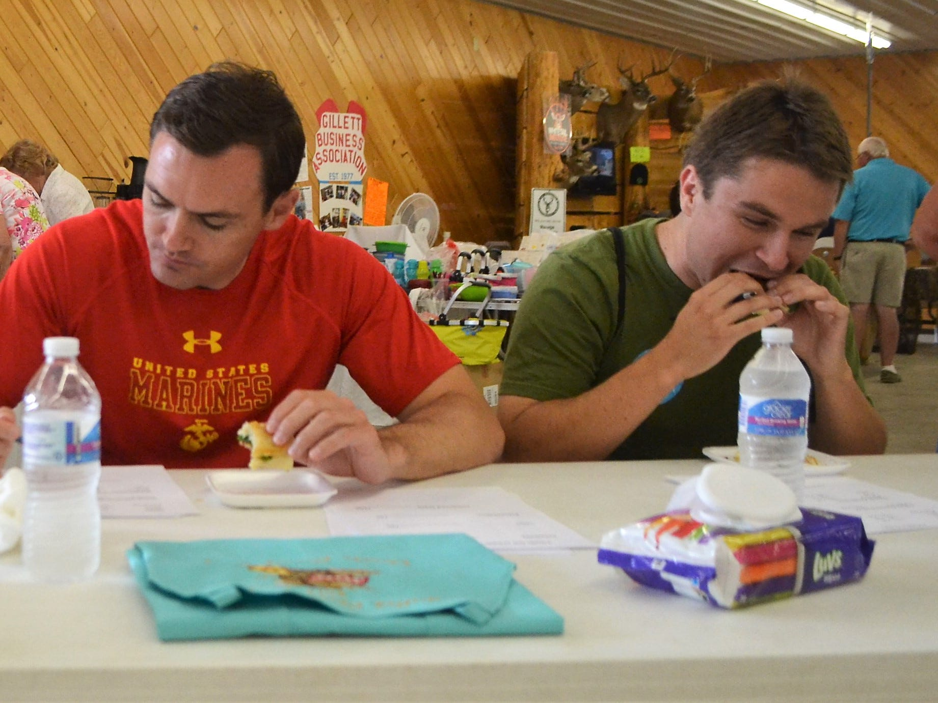"Max Morales, right, of Green Bay, digs into a grilled sandwich as one of the judges of the Creative Grilled Cheese Sandwich competition at the Oconto County Fair on Saturday, Aug. 18. The other judges were, from left Phil Dickson of the Oconto County Fair Board, and U.S. Rep. Mike Gallagher, who are filling out score sheets. Morales, an organizer for the Democratic Party in the area, quipped that judging with Gallagher ""is our bipartisan cooperation for the day."""
