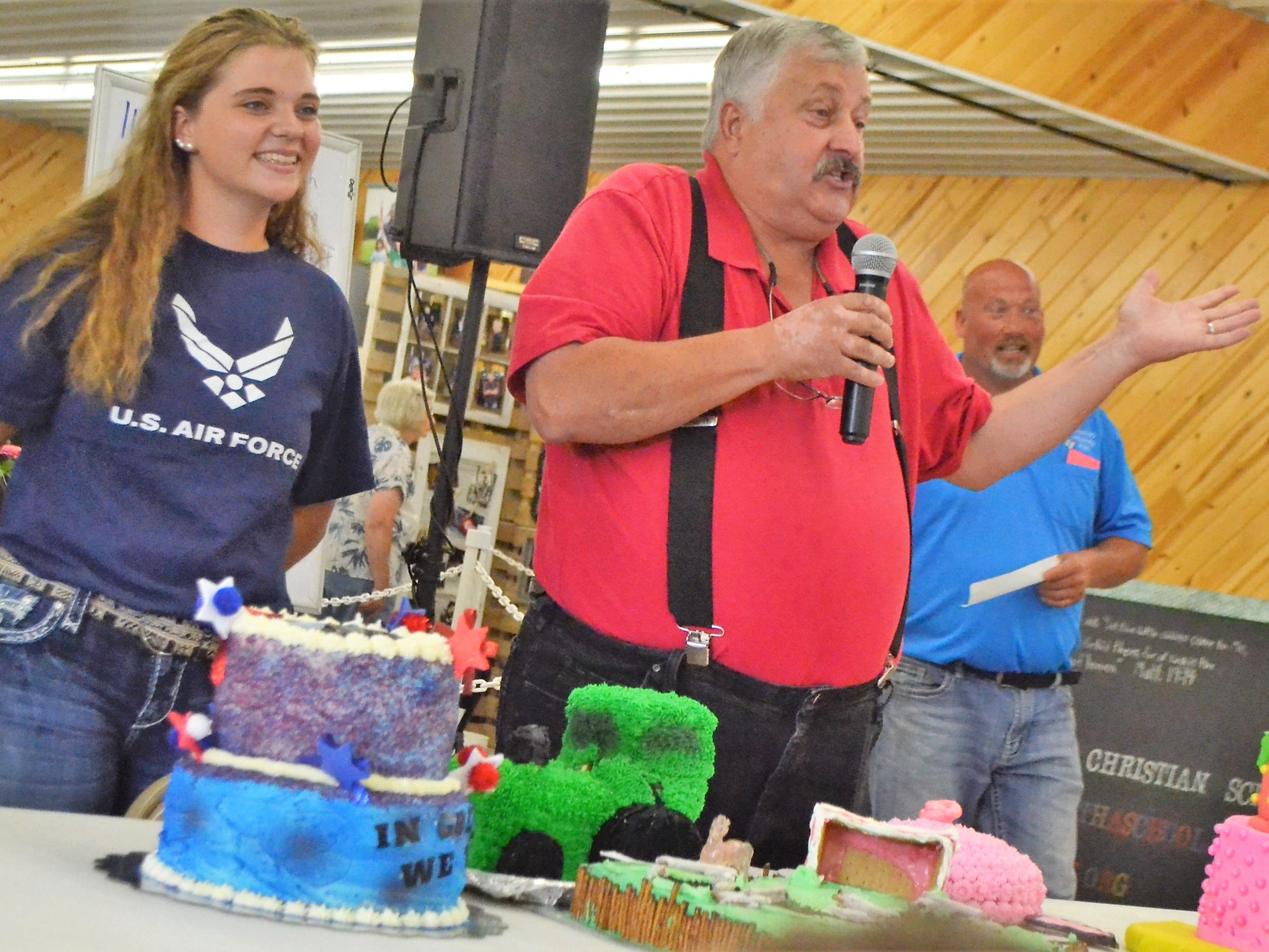 Auctioneer Jeff Bahrke of Gillett urges a higher bid  for the cake of Hannah Brock, left, during the Decorated Cake Auction at the Oconto County Fair on Saturday, Aug. 18. Brock made the cake, with a military theme, because she was entering the Air Force in a few weeks, and she wanted to donate the proceeds to Wounded Warrior Project. The cake was purchased by her grandfather, Russel Brock, for $775, who  donated the cake back to be auctioned again, with proceeds being donated to the fair. The cake was sold then for $400.