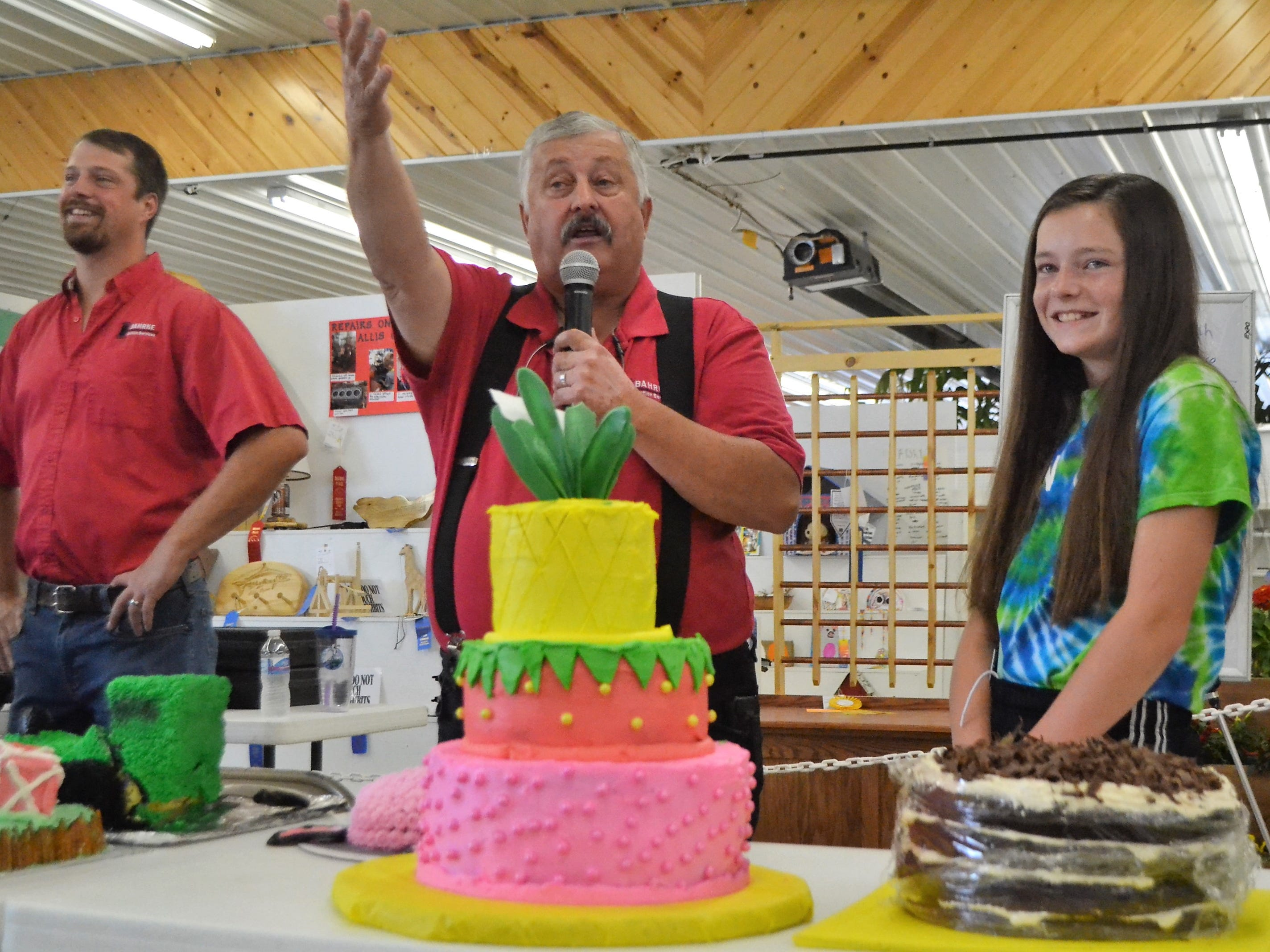 Katy Raddatz, 12, of Oconto Falls, a member of Christy Brook 4-H Club, smiles as auctioneer Jeff Bahrke of Gillett tries to elicit a higher bid of her huge cake at the Decorated Cake Auction at the Oconto County Fair on Saturday, Aug. 18. The cake, at center front, with layers of lemon, strawberry and vanilla (with raspberry filling!) weighed 27 pounds. It sold for $575, which Katy said would go into her college fund. At left is Jeff's son, fellow auctioneer John Bahrke.