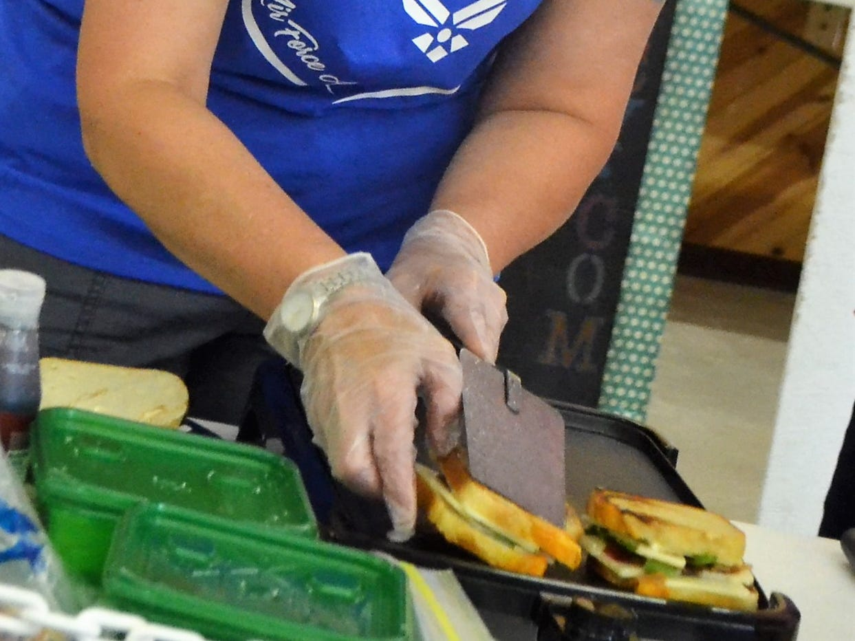"Theresa Wrolstad of Sobieski flips one of her ""Italian Stallion"" sandwiches in the Creative Grilled Cheese Sandwich competition at the Oconto County Fair on Saturday, Aug. 18. The winner among five competitors was Jenny Neumann of Gillett, who along with ""lovely assistant"" Gabby Wellnitz, prepared ""The Pig Cheese,"" which featured two kinds of cheese, pulled pork and bacon on Texas toast."