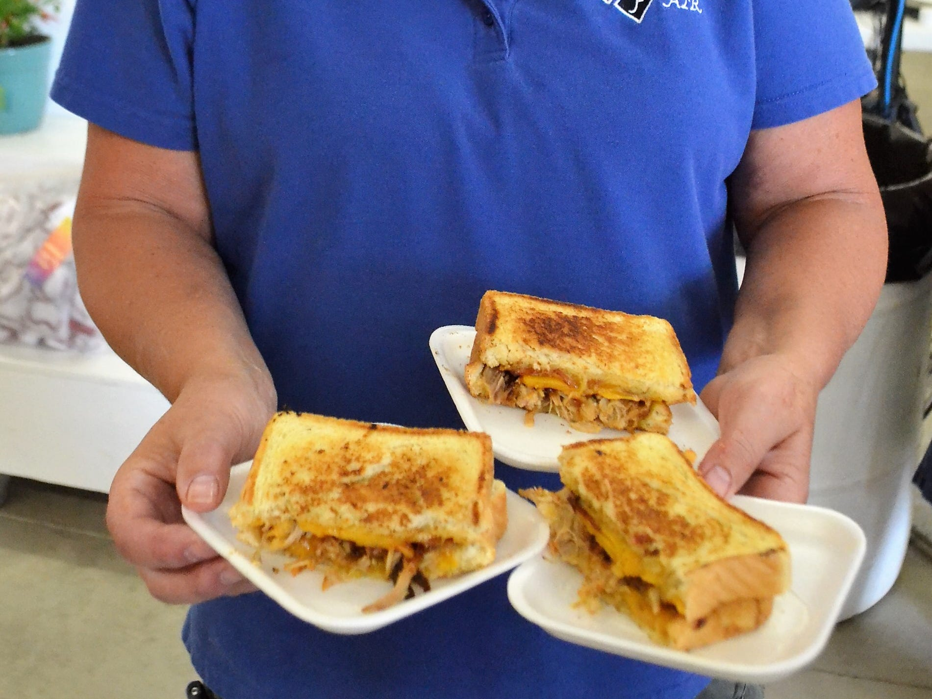 "Oconto County Fair Board secretary Clara Luther holds three samples of the ""The Pig Cheese"" to be delivered to judges for tasting at the Creative Grilled Cheese Sandwich Contest at the Oconto County Fair on Saturday, Aug. 18. The sandwich, made by Jenny Neumann of Gillett, was named the winner."