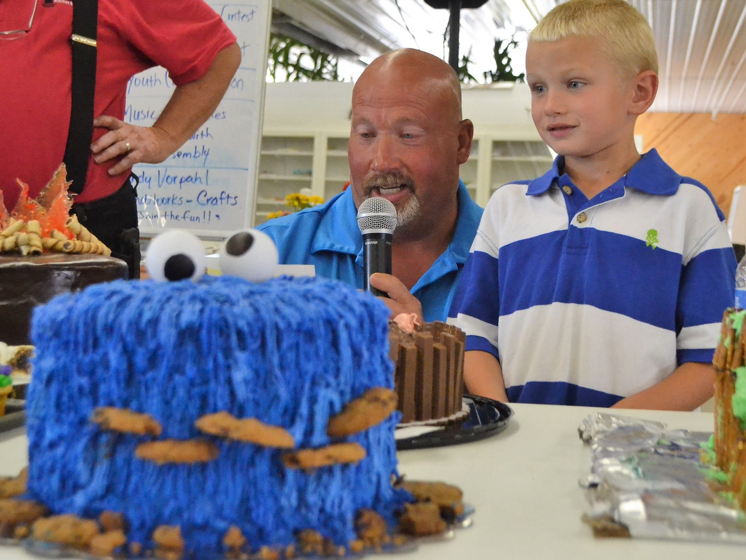 Chris Engebretson introduces his son Connor's cake at the Decorated Cake Auction at the Oconto County Fair on Saturday, Aug. 18. The Cookie Monster theme cake fetched $1,400, purchased by a group of five people.  Half of the money will go to the draft horse pull held Saturdays at the fair, which Connor enjoys, with the rest going for future fair projects.