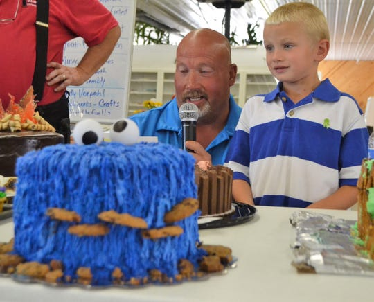 Chris Engebretson introduces his son Connor's cake at the Decorated Cake Auction at the Oconto County Fair on Aug. 18. The Cookie Monster theme cake fetched $1,400, purchased by a group of five people. Half of the money will go to the draft horse pull held Saturdays at the fair, which Connor enjoys, with the rest going for future fair projects.