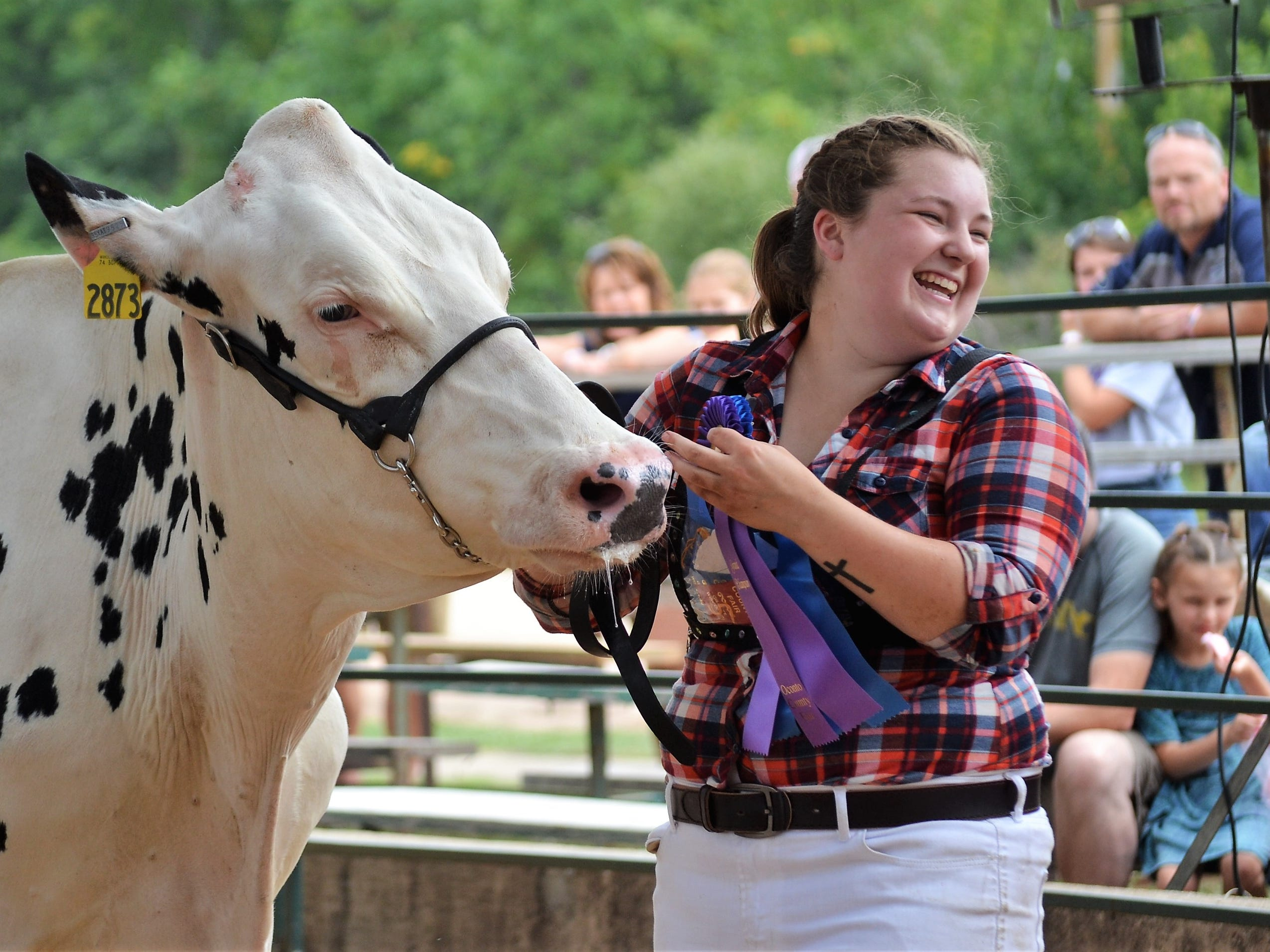 Alexandra Raddatz of Christy Brook 4-H Club smiles after winning both overall  Grand and Reserve Champion awards in the Junior Dairy Cattle Competition at the Oconto County Fair on Saturday, Aug. 18.
