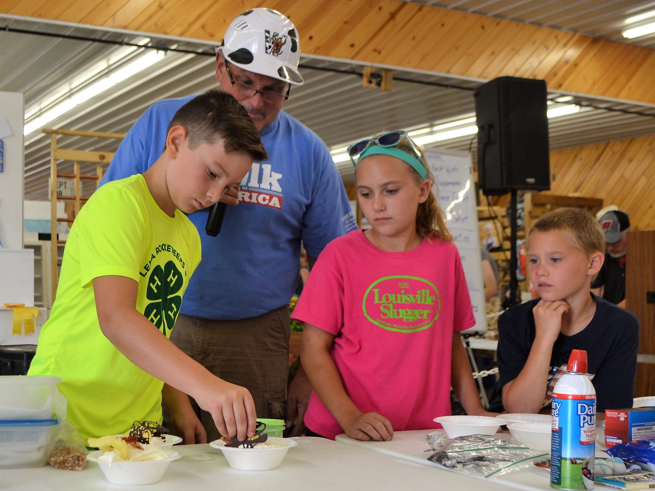 Vance Turcek, 11, of the Lena Rocketeers 4-H Club, places a piece of chocolate on top of sundae for judges in the Ice Cream Sundae competition at the Oconto County Fair on Saturday, Aug. 18. At right are the other two entrants, siblings Josie Holtz, 11, and Isaiah Holtz, 9, of Oconto Falls and members of Willing Workers 4-H Club. Looking on is Mark Alden of the Oconto County Dairy Promotion Board. Josie Holtz won first place.