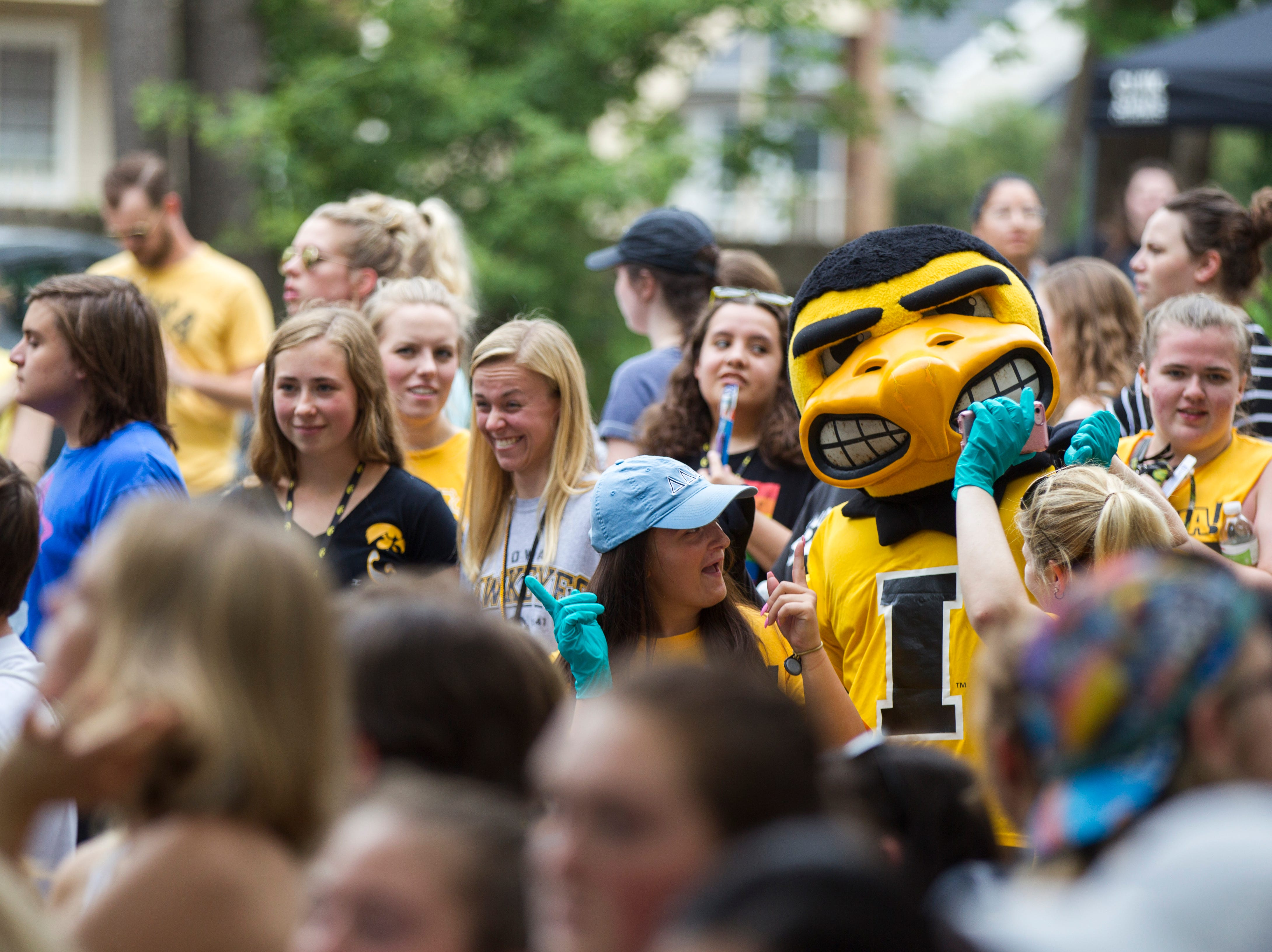 Herky the Hawk dances with volunteers during the University of Iowa class of 2022 block party on Sunday, Aug. 19, 2018, along Church Street in Iowa City.
